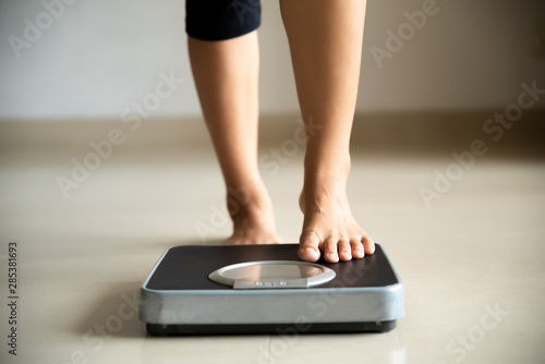 Photo Female leg stepping on weigh scales