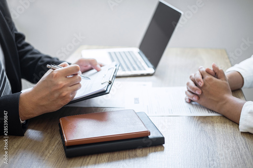 Obraz Employer or committee holding reading a resume with talking during about his profile of candidate, employer in suit is conducting a job interview, manager resource employment and recruitment concept - fototapety do salonu
