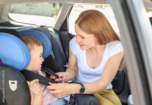 Photo  Mother buckling her little son in car seat