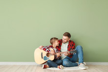 Portrait Of Happy Father And Son With Guitar Sitting Near Color Wall
