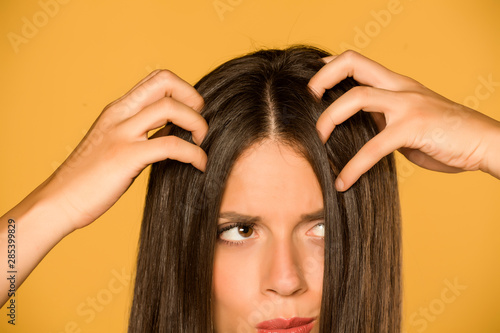 Fotografía  Beautiful young woman with itchy scalp on yellow background