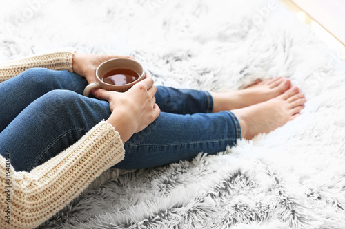 Spoed Fotobehang Thee Young woman drinking hot tea at home