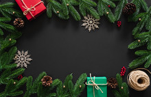 Christmas Background With Decoration, Red And Green Gifts, Snow Flake ,berries, Pine Branches And Cones, Rope On Black Background With Center Copy Space