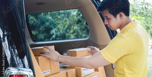 Fotografiet  Young Asian Delivery man checking list of package boxes
