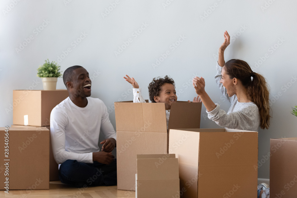 Fototapety, obrazy: Happy mixed ethnicity family playing on moving day unpacking boxes