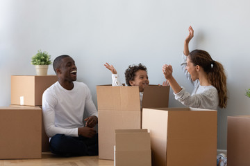 Happy mixed ethnicity family playing on moving day unpacking boxes