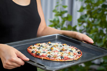 A Girl In An Black T-shirt Is Holding Just Cooked Homemade Pizza On Metal Pan Outdoors. Pizza With Shrimp, Mussels, Black Olives And Mozzarella. Home Holiday Cooking. Closeup, Selective Focus