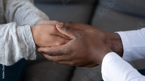 Close up of african husband holding hand of white wife Canvas Print