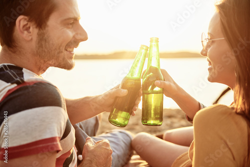 Poster de jardin Bar Young couple drinking beer on the beach