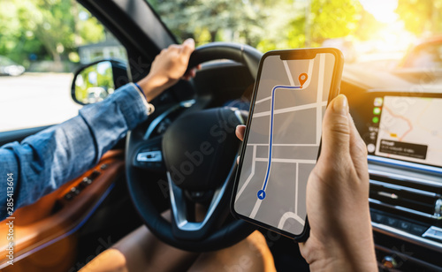Tourist using GPS map navigation app on smartphone screen to get direction to de Fototapeta
