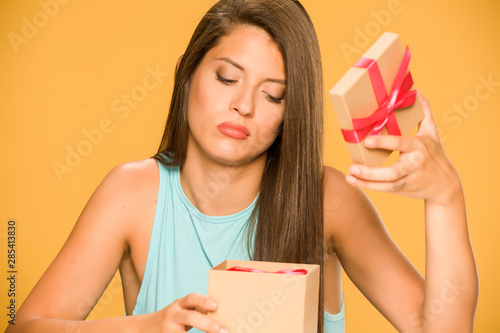 Fényképezés Young disappointed woman opening a present box on yellow background