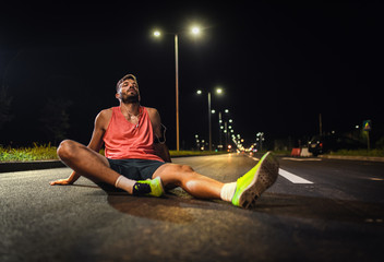 Male runner resting after night workout in the city.