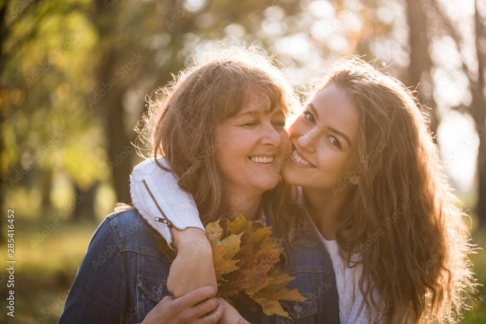 Fototapeta Daughter hugging her mother in nature