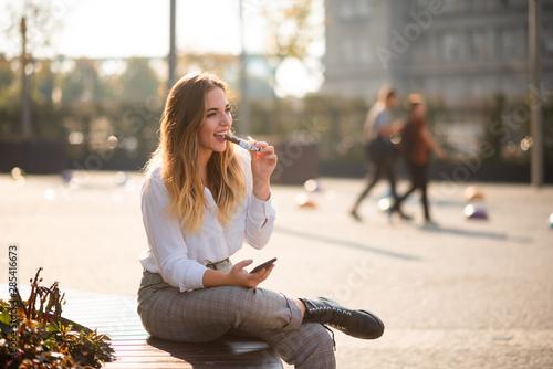 Foto Happy girl having bite of energy bar, candid shot.