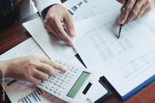 Photo Businessman analyzing investment charts and pressing calculator buttons over documents