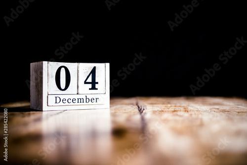 December 4th, 4 December, Fourth of December - White block calendar on vintage table - Date on dark background