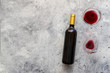 Red wine bottle with red wine glass on concrete background. Top view Copy space.