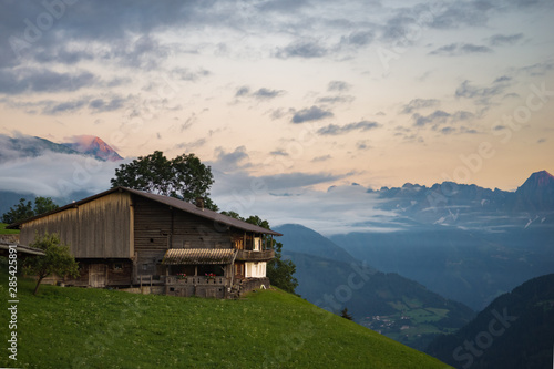 Chalet in the Alps at sunset with alpenglow on top of the mountains Wallpaper Mural