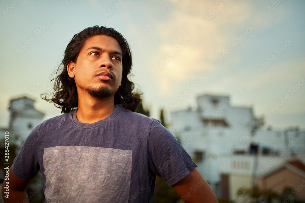 Fototapeta Handsome long hair young man standing in evening light