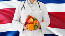 Doctor Is Holding Fruits And Vegetables In Hands With Costa Rica Flag Background. National Healthcare Concept, Medical Theme.
