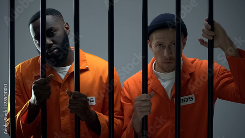 фотография Caucasian and afro-american prisoners holding jail bars and looking to camera