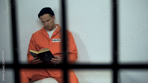 Canvas Print Caucasian prisoner reading bible in cell, convicted sinner turning to religion