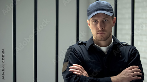 Photo Brave jail guard looking at camera standing near cell, dangerous occupation