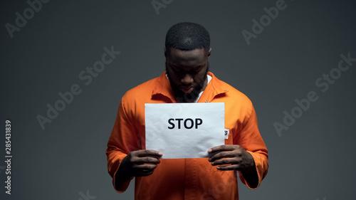 Afro-american prisoner holding stop sign, racial discrimination, persecution Fototapet