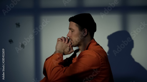 Fotografering Guilty male prisoner praying with eyes closed, asking for mercy and freedom