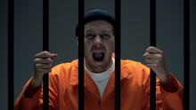 Aggressive Dangerous Male Prisoner With Scar On Face Holding Bars And Shouting