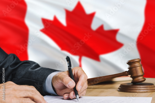 Fotografie, Obraz  Judge writing on paper in courtroom with Canada flag background