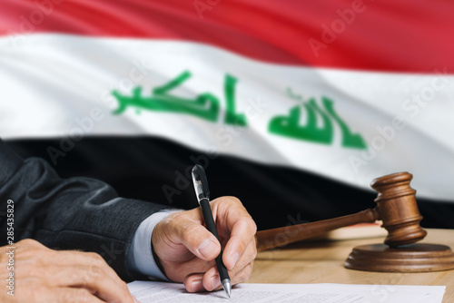 Judge writing on paper in courtroom with Iraq flag background Canvas-taulu