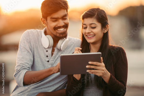 Cheerful young friends using tablet with headphones Wallpaper Mural