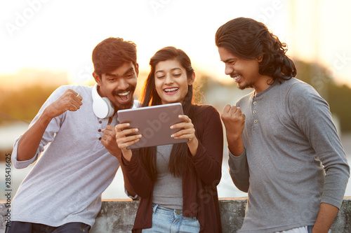Vászonkép Cheerful young Indian friends playing in digital tablet