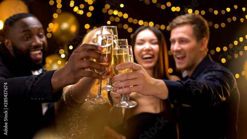 Fotografie, Obraz Cheerful multi-racial friends clinking champagne glasses, corporate event, fun