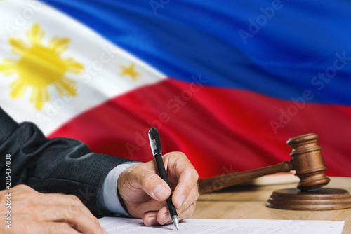 Fényképezés  Judge writing on paper in courtroom with Philippines flag background