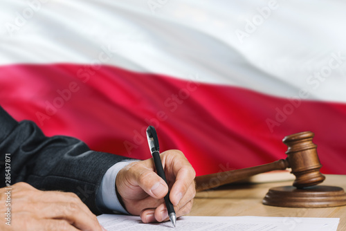 Fotografía  Judge writing on paper in courtroom with Poland flag background