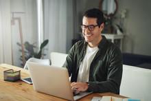 Happy Man Wearing Eyeglasses Using Laptop At Home