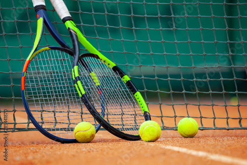 Canvas Print Tennis rackets and balls leaned against the net.