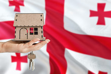 Woman Hand Holding Wooden House And Keys With Hand. Georgia Flag With Concept Of Rent, Purchase, Insurance, Building Real Estate, Eco House.