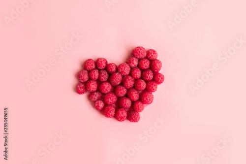 Fényképezés  Red raspberries in a heart shape on pink background