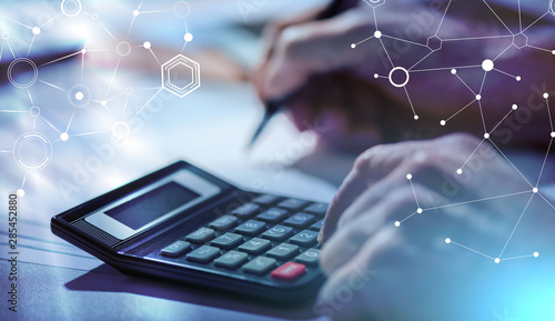 Hand using calculator, accounting concept; light effect Wallpaper Mural