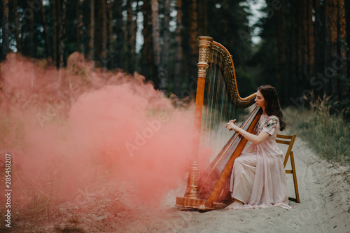 Tablou Canvas Woman harpist sits at forest and plays harp against a background of pines and smoke
