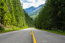 Empty Straight Stretch Of A Mountain Road Through A Dense Pine Forest And Cloudy Sky
