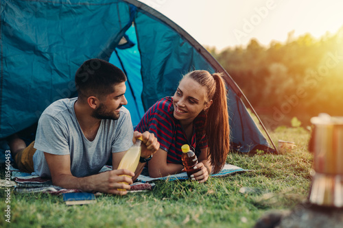 young couple talking and drinking juice while camping outdoor - 285460453