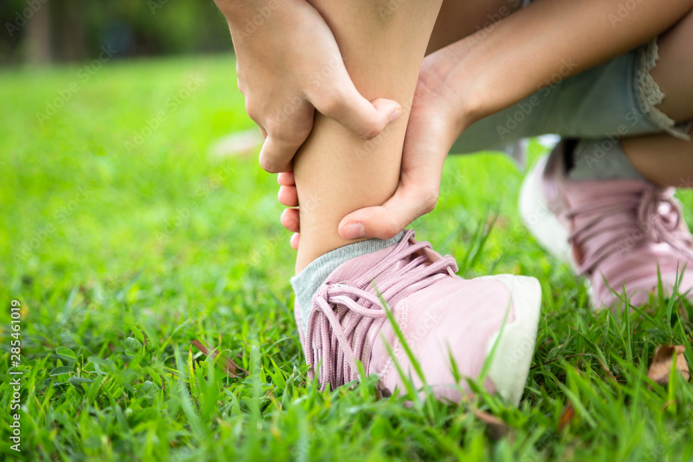 Fototapeta Female hand touching painful twisted or ankle sprain,feel ache,ankle injury after exercise at park,asian child girl have leg pain or broken ankle,problem,accident while running,playing on the lawn