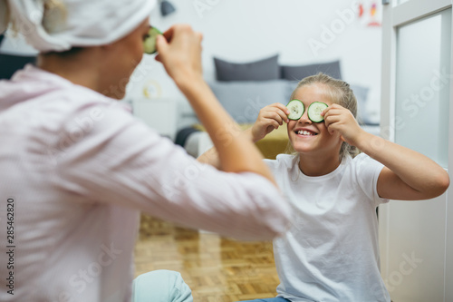 Obraz na plátně  mother and daughter applying cosmetic face mask at home