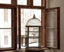 Silhouette Of An Empty Vintage Bird Cage Standing In A Window Sill With Wooden Window Frames
