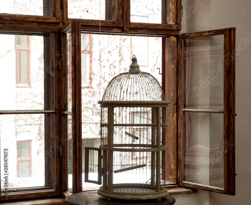 silhouette of an empty vintage bird cage standing in a window sill with wooden w Fototapet