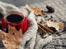 Hygge Style. The Comfort Of Home, Coffee Mug, Wrapped In A Knitted Scarf Is A Homemade Knitted Wool Sweaters . Autumn Or Winter Still Life